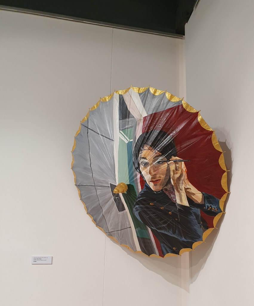 Oil painting on parasol hanging in a gallery